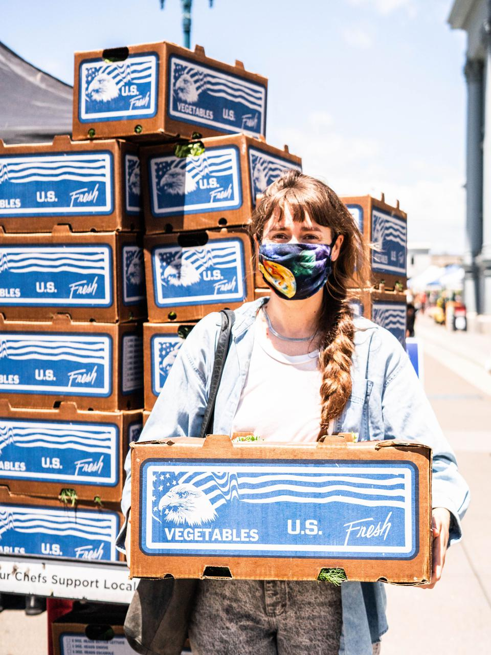 Woman in mask holding a cardboard box labeled ″vegetables.″