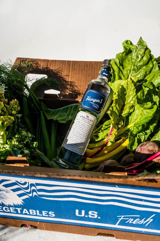 Box of vegetables with a bottle of Hangar 1 vodka inside.