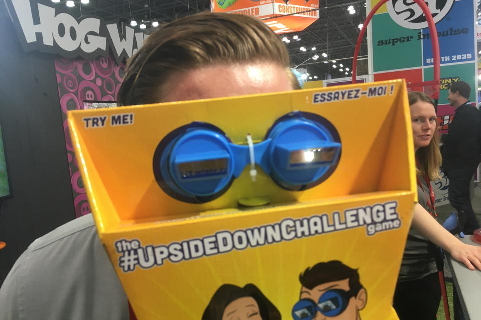 Josh Loerzel of Hog Wild trying on the Upside Down Challenge goggles, which make things appear upside down, at New York toy Fair, February, 2020.