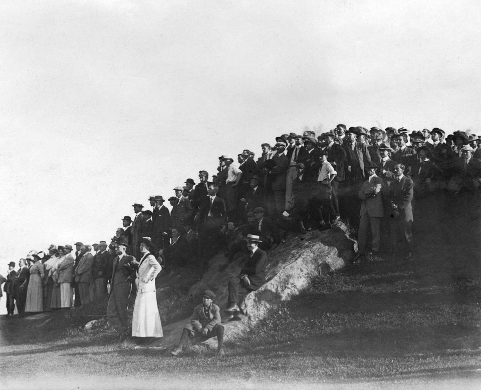 large group of spectators stand on a mound near the fairway watching the 1911 U.S. Amateur
