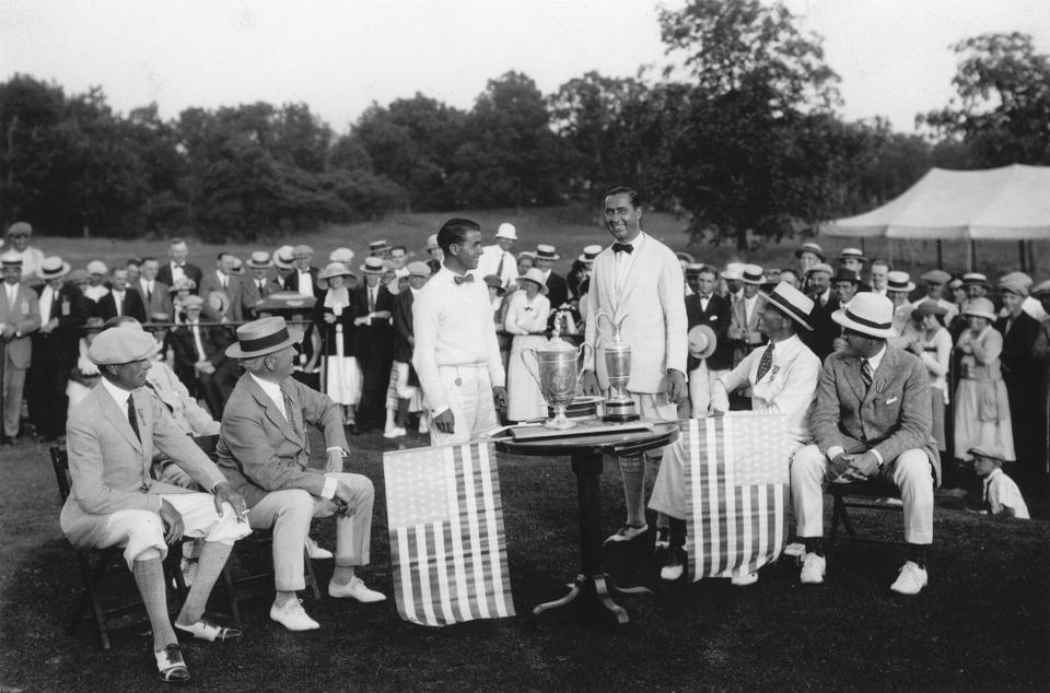 Walter Hagen and Gene Sarazen standing in front of trophies with a gallery looking on.