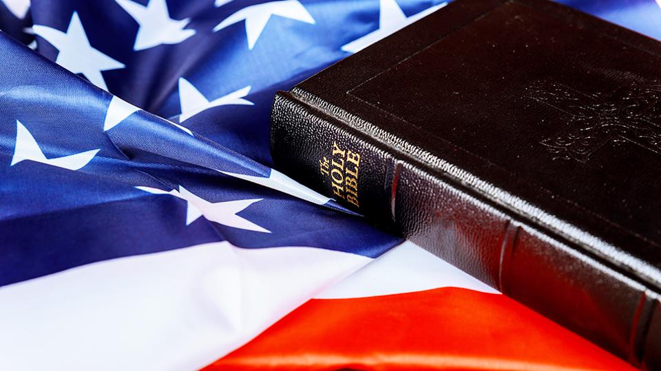 a copy of the holy bible lying on top of an american flag