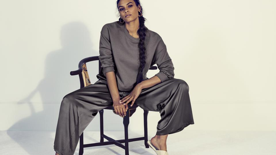 Woman in sweatshirt and satin pants sits on chair