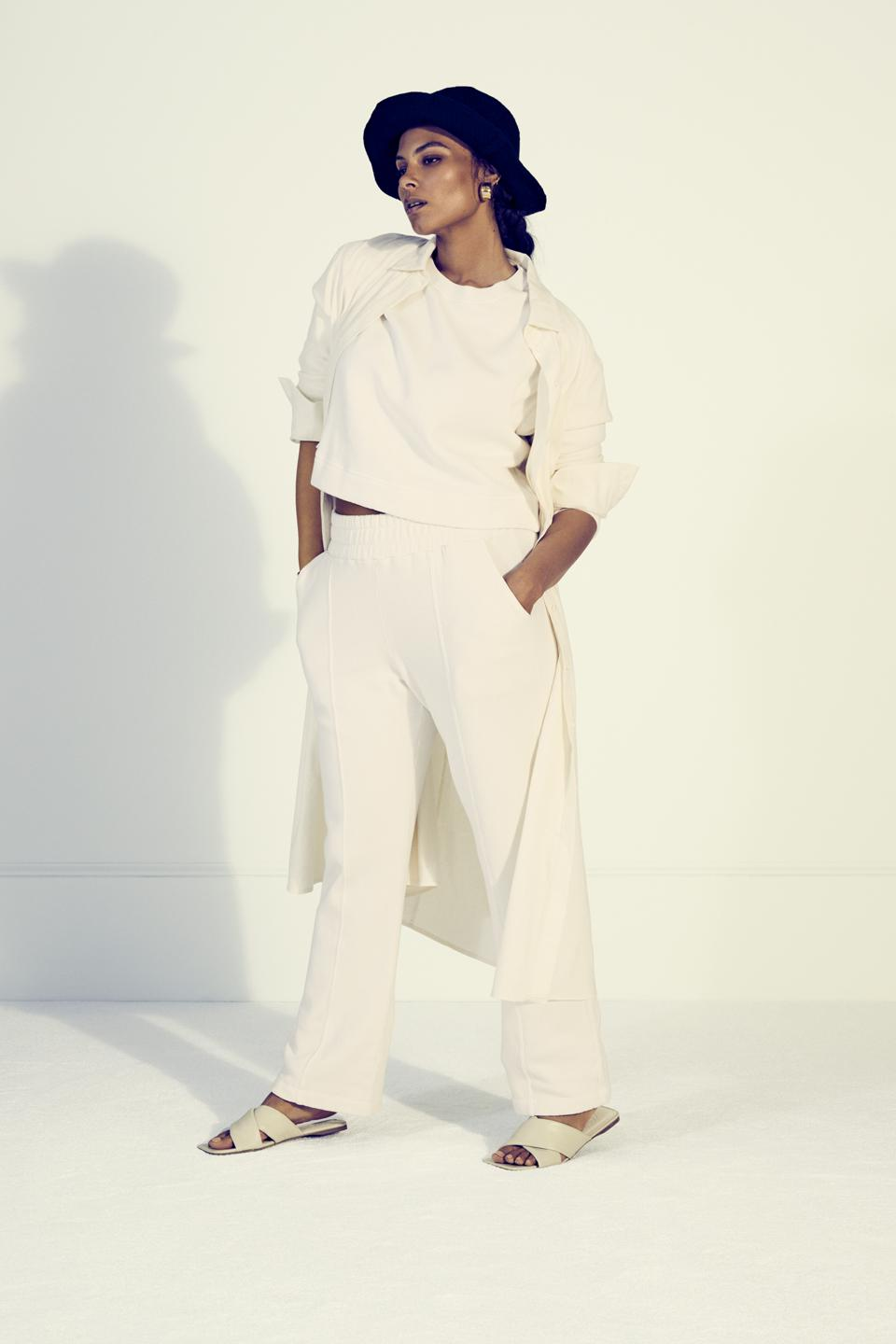 Woman in hat with hands in her pockets wearing cream pants and cropped sweatshirt with sandals.
