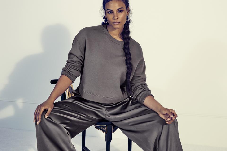 Woman looking at camera in satin pants and sweatshirt.