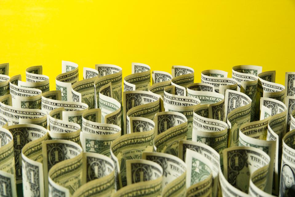 Sea of US 1 dollar bills on yellow background