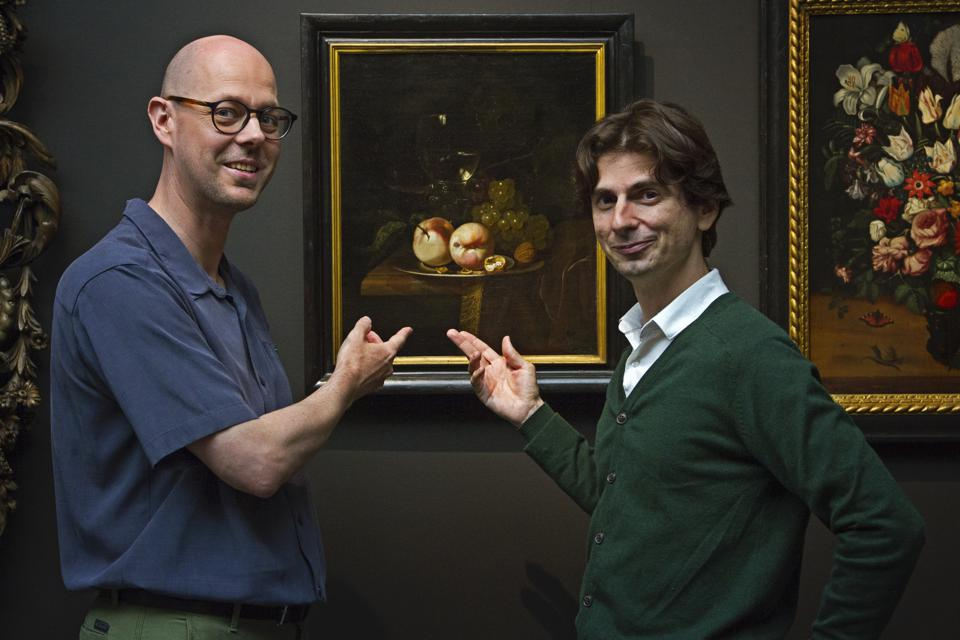 Two men stand in front of a still life painting of fruit.