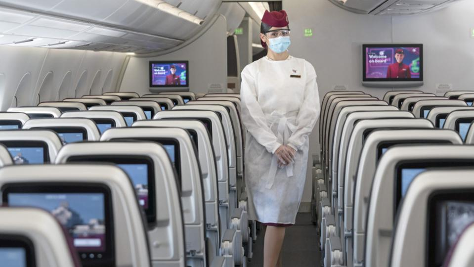 Qatar airways cabin crew wearing mandatory mask and face shield on airplane.