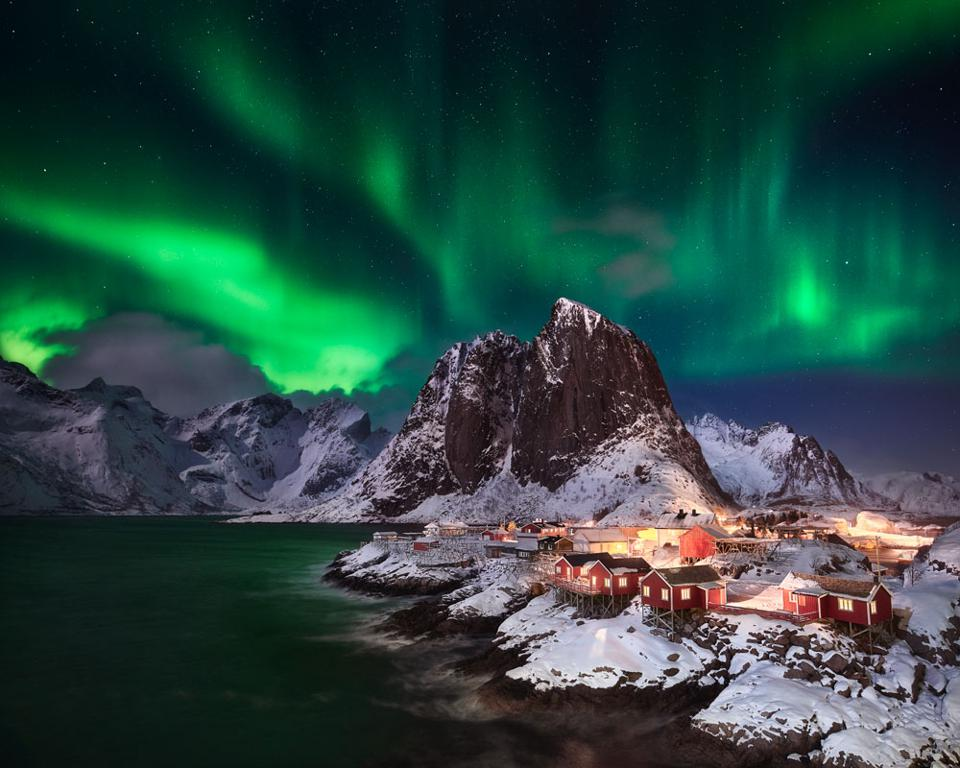 Hamnøy Lights: After two weeks of storm, clouds and snow in the Lofoten Islands, the sky finally cleared up, providing perfect conditions for hunting the northern lights. The photographer waited patiently in their car for the light show to begin and on the first sign of the aurora borealis in the sky, he set up his camera at this famous overlook of the idyllic fishing village Hamnøy. The image is a manual exposure blend consisting of one base image for the sky and foreground plus a total of seven bracketed images to balance the highlights and shadows in the fishing village and water.