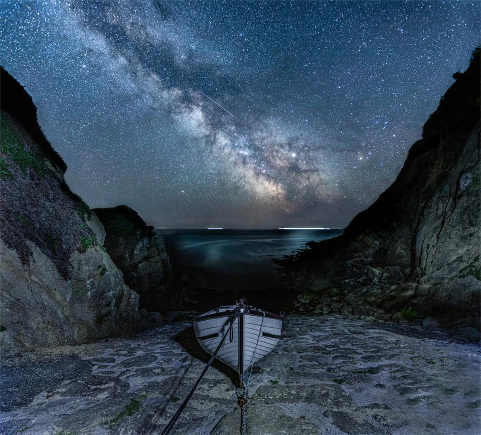 Milky Way and Meteor at Porthgwarra: Porthgwarra is a sheltered fishing cove in the west of Cornwall and the U-shape of the narrow cove is perfect for framing the Milky Way. There was likely to be a boat in the cove but the photographer was very fortunate to find it perfectly positioned in the centre of the old slipway. The photographer shot several non-tracked sky exposures from the same tripod position to capture the cliffs and horizon (as these were blurred in the tracked shot) and in one, she was lucky enough to capture a meteor, which she copied into the final image. This is one of the photographer's favourite locations in Cornwall and it was a magnificent night under the stars.