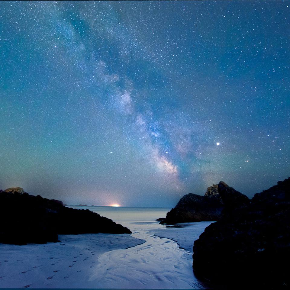 Kynance Cove under the Milky Way: This image is only the photographer's second attempt at shooting the Milky Way. It shows our galaxy over Kynance Cove in Cornwall, a beautiful spot with dark skis. It was taken on a cold, but fabulous night under the stars. As it was July, the sky was very blue, with full darkness only for about an hour. The foreground was taken at dusk and the sky is a stack of 4 images of 25 seconds taken later when the Milky Way appeared, the sky and foreground blended together in post processing.