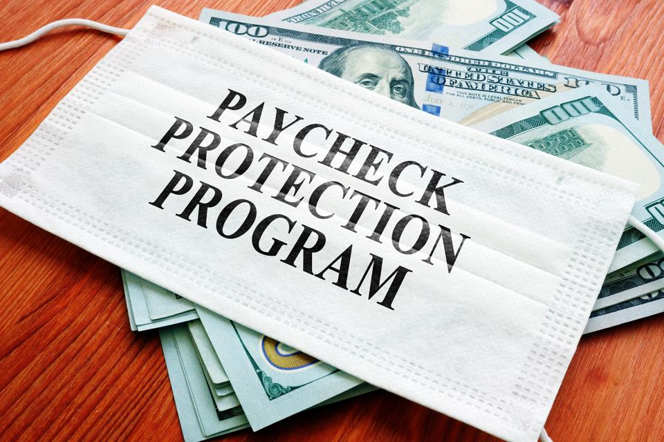 PPP Paycheck Protection Program as SBA loan written on the mask and money.