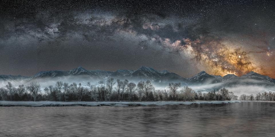 Cold Night on the Yellowstone: In mid-March, shortly after the core of our galaxy is visible above the horizon, it rises in the final hours of darkness before dawn. Shooting this panorama scene, while night-time fog hung low over riverside cottonwood trees and the distant mountains of the Absaroka Beartooth Wilderness glowed from the light of countless stars, the photographer felt that he was able to capture a connectedness between this world and the one above – a hint of changing seasons, and a sense that Nature continues to provide countless wonders for all willing to stop and look.