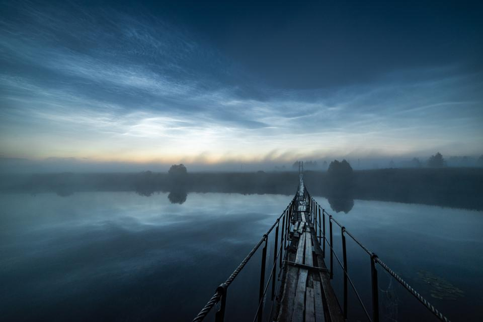Beyond the Fog: the photographer had to wait, drenched on a rickety bridge until the thick fog had cleared. He was rewarded with noctilucent clouds in the sky, the outlines of which were reflected in the mirror of the calm river. The photographer's patience paid off as he caught the last outline of the departing mesospheric storm.