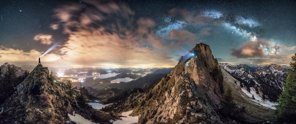 Meeting: After a long hike and a little bit of climbing to the top of the mountain, the photographer was able to see the Milky Way. He only had five minutes time to take the panorama shot before the clouds moved. The photographer and his friend are pictured standing on the edge, looking out at the sky and over the city of Füssen in Germany.