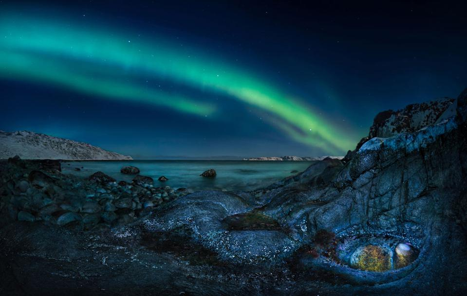 Northern Dragon's Eye:The photographer loves to travel, especially exploring the north and chasing the Northern Lights. Trying to capture how ordinary things can take magical forms under the lights, the photographer selected and lit this rocky outcrop and waited for the aurora to work its magic.