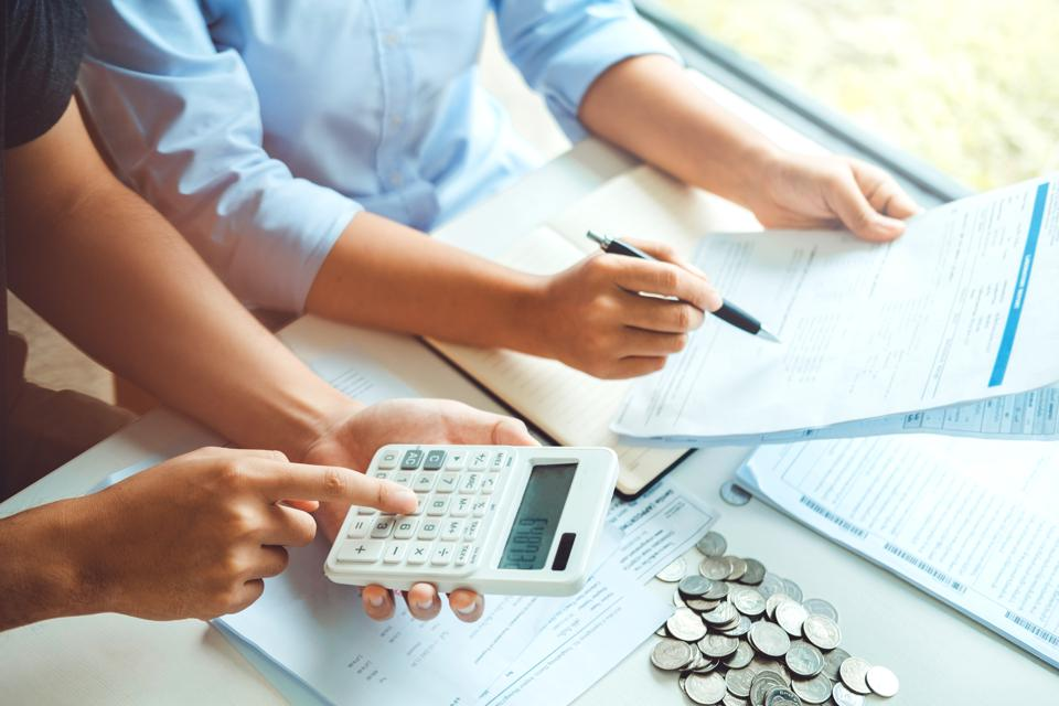 Couple using calculator Accounting Calculating Cost Economic bills with money stack step growing growth saving money in home , finance concept