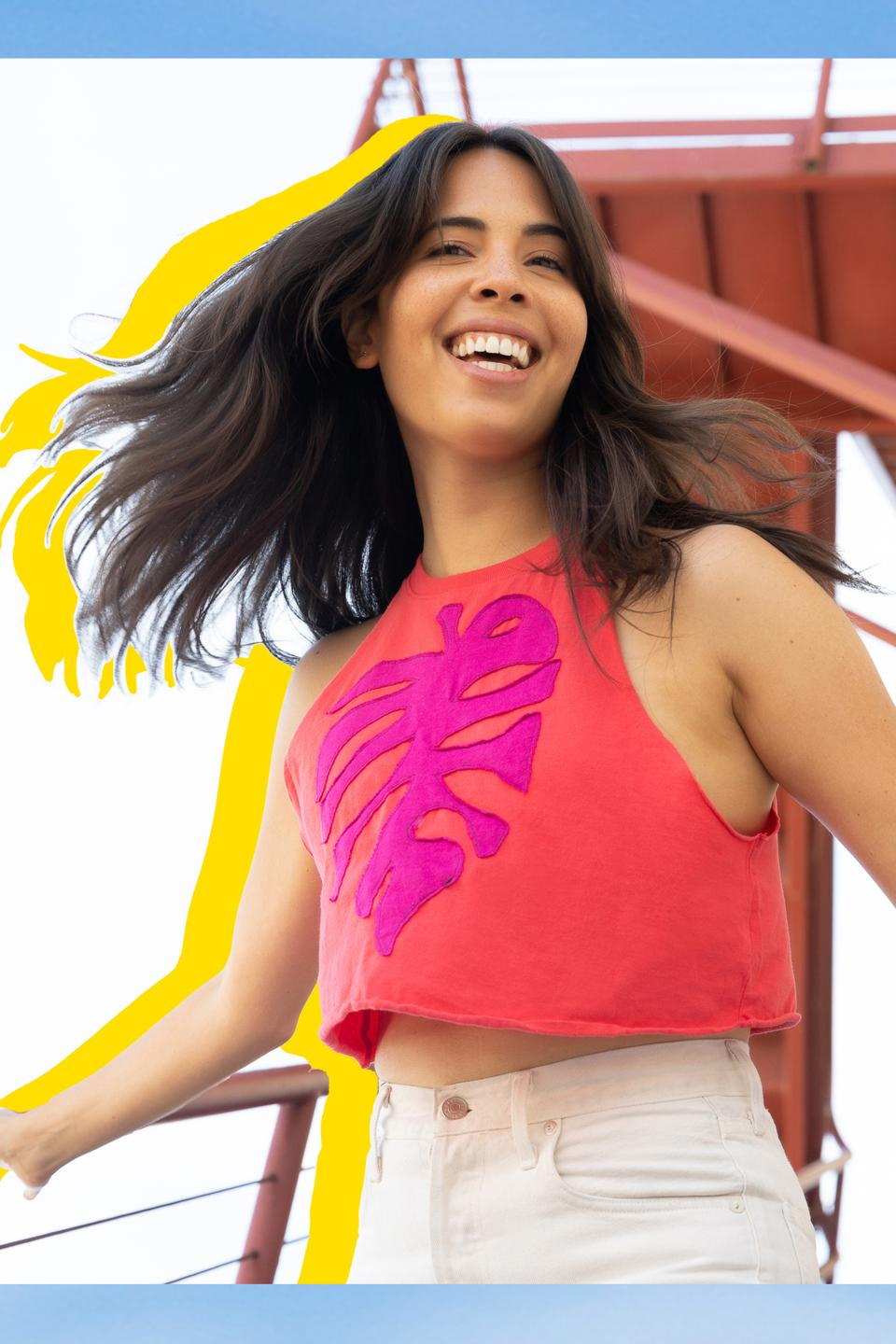 A model wears a red sleeveless crop top with fuchsia leaf from ThredUP x Zero Waste Daniel.