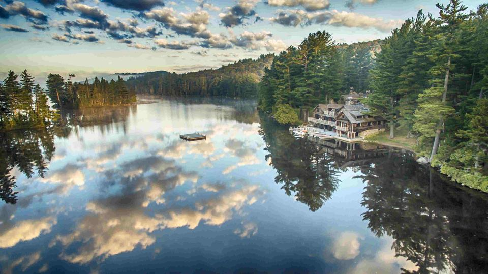 A wooden lodge facing a lake in the Adirondack Region of New York State
