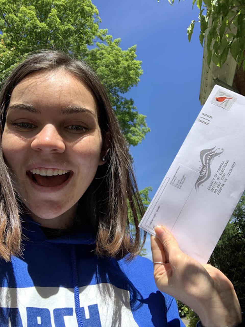 A female student in a blue tshirt votes by mail.