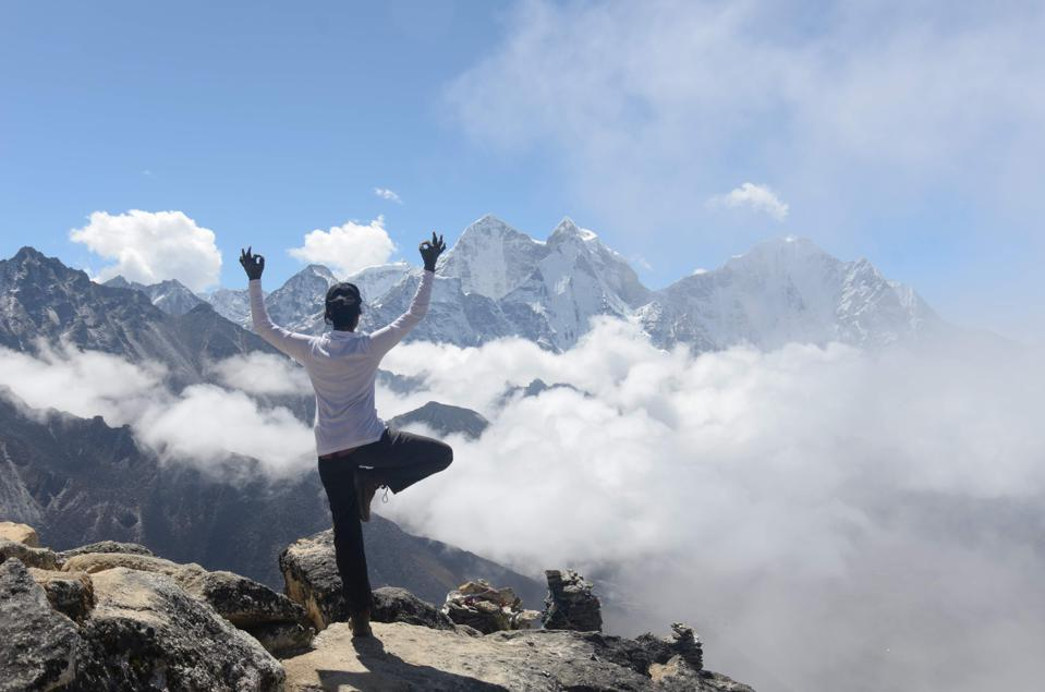 Amiti doing yoga on the top of a mountain.