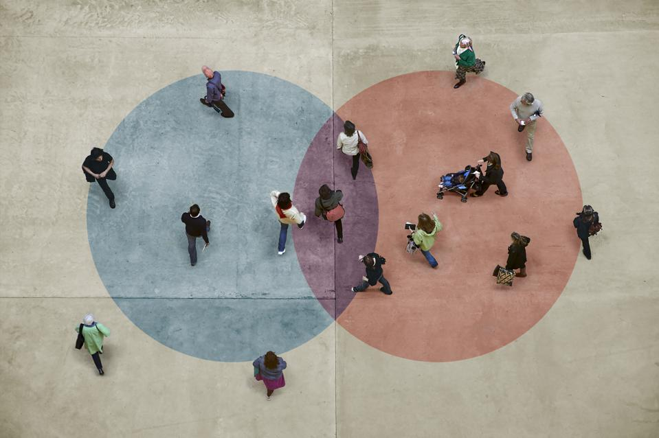 Pedestrians on a concrete floor with a blue and red Venn diagram.