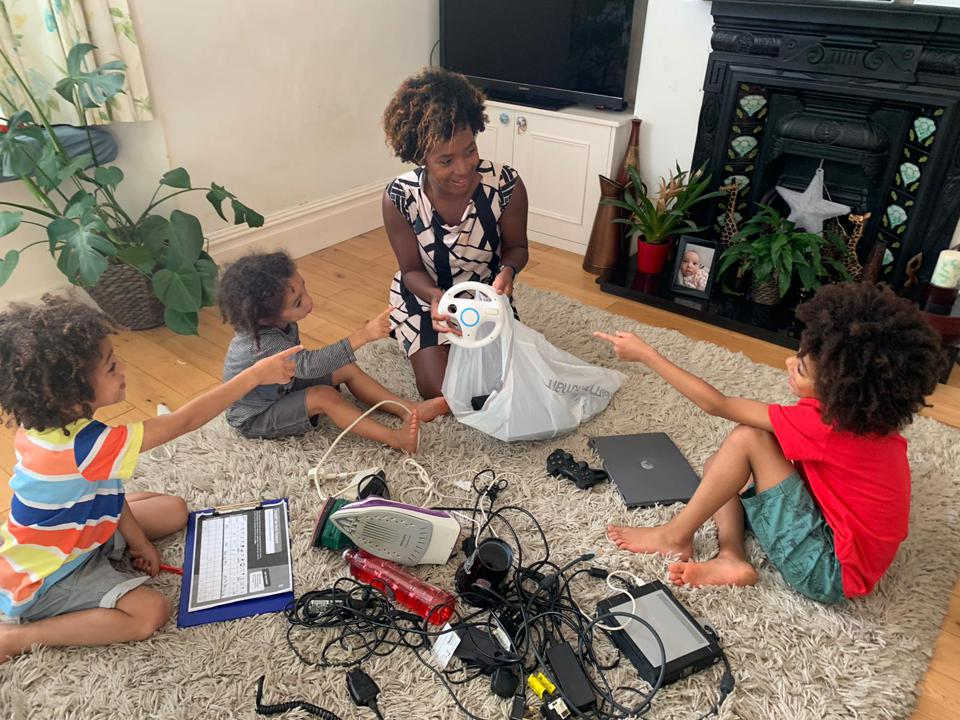 Liz Piggott and her three young sons look through old electrical devices in their home.