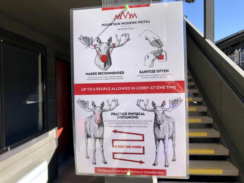 Signage at a Wyoming motel uses moose to model mask, cleanliness and physical distancing.