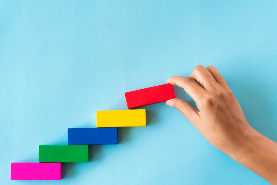 Cropped Hand Of Person Playing With Toy Blocks Against Blue Background