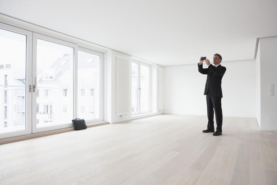 Estate agent standing in empty apartement, taking pictures