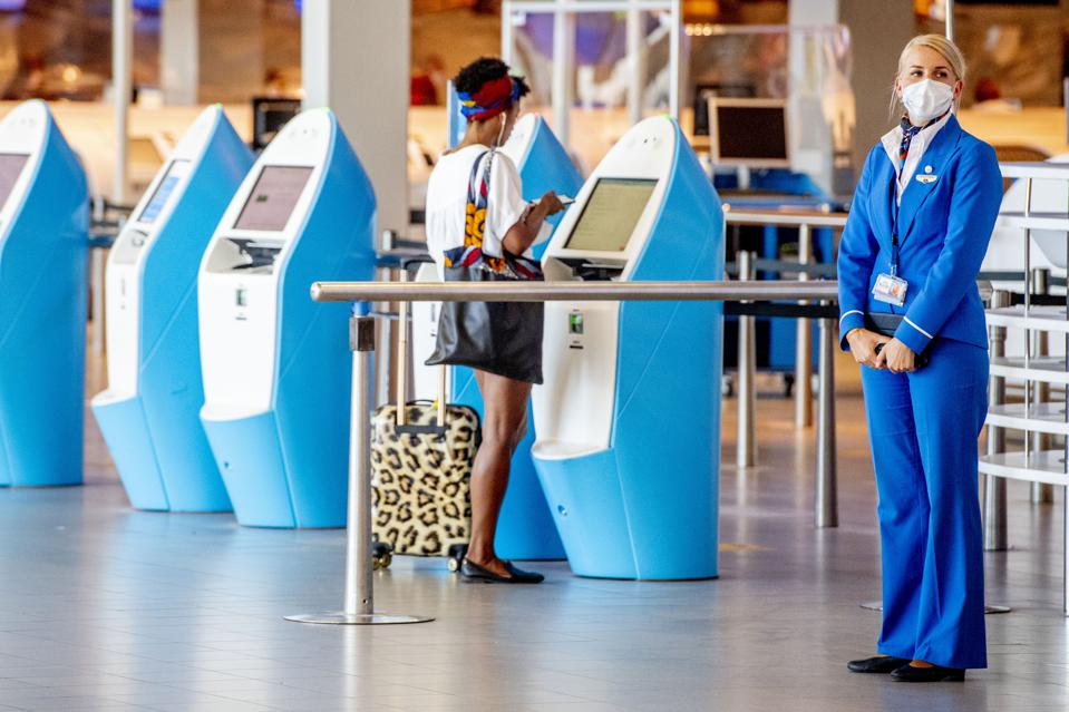 An airline staffer wearing a mask stands at attention while a woman checks in at an airport kiosk
