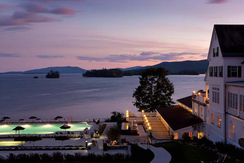 Sunset on Lake George, with a pool in the foreground and a house.