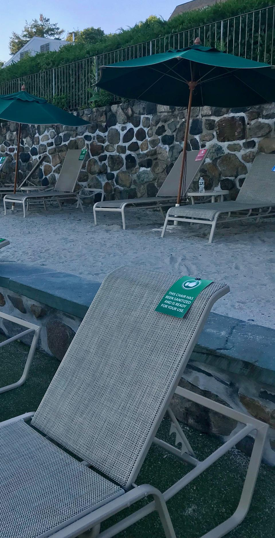 a lounge chair with a green card that says the chair has been sanitized