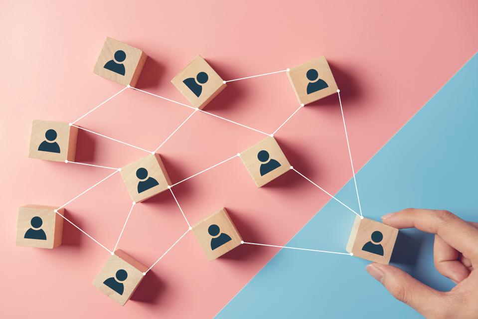 Building a strong team, Wooden blocks with people icon on pink and blue background, Human resources and management concept.