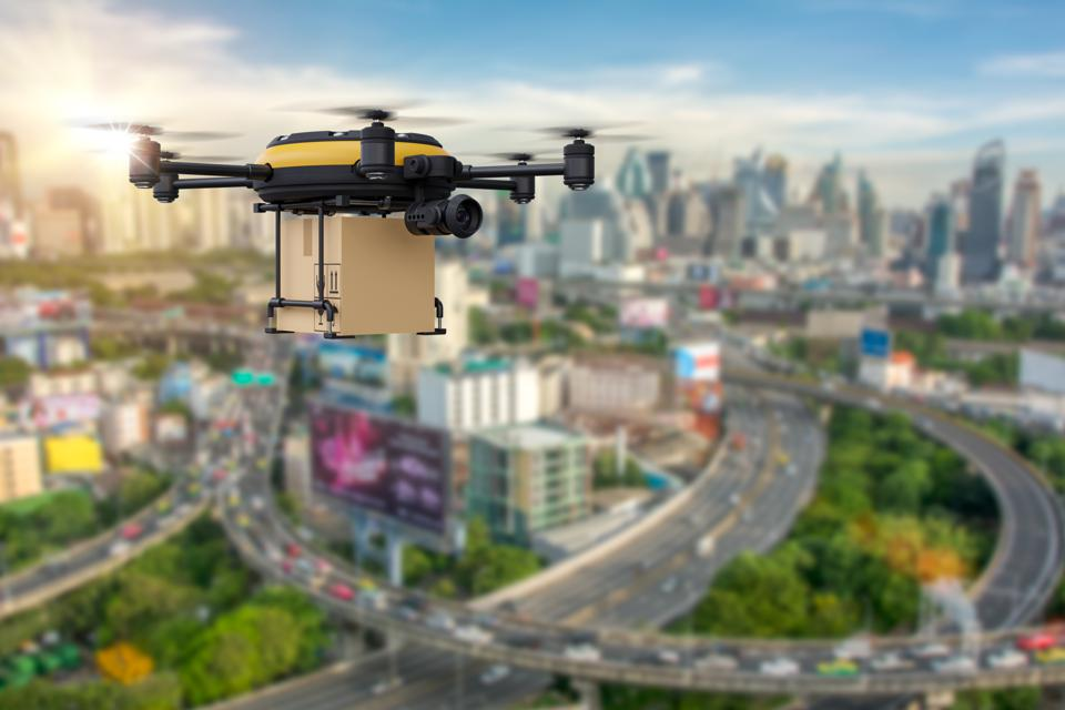 Delivery drone with the package against city background. Fast and convenient transportation concept.