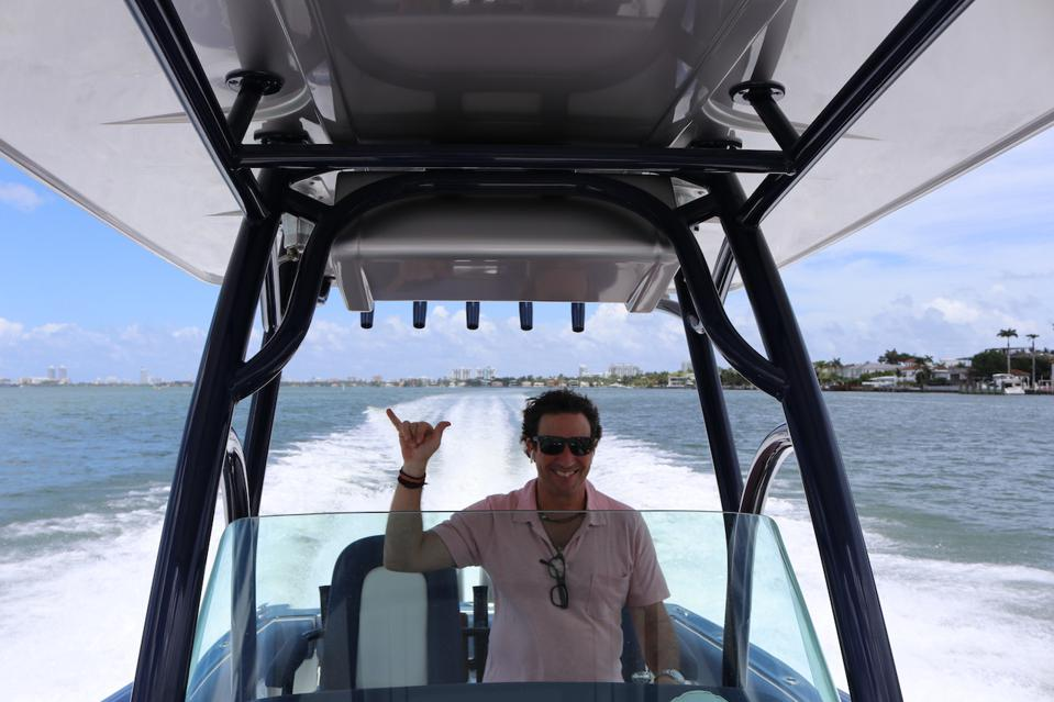 Miky Grendene at the helm of his dual outboard Chris Craft center console powerboat that's available for charter through Casa Tua.