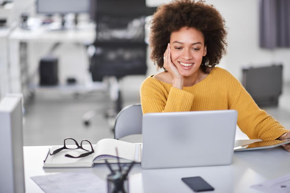 Businesswoman looking at laptop while sitting in office.