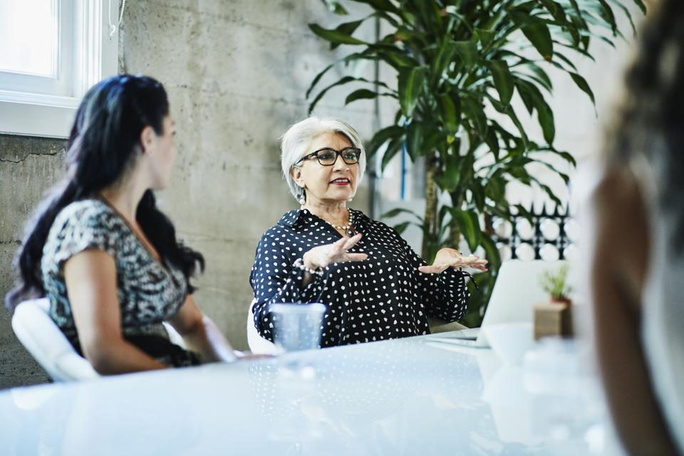 Mature female business owner leading team discussion during project meeting in conference room