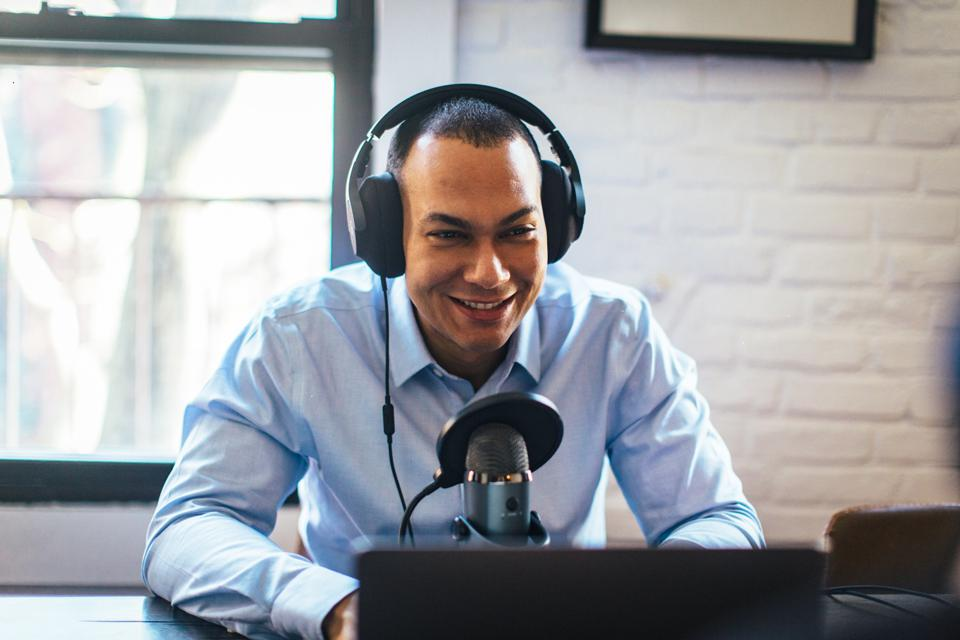 Coss Marte podcasting wearing headphones