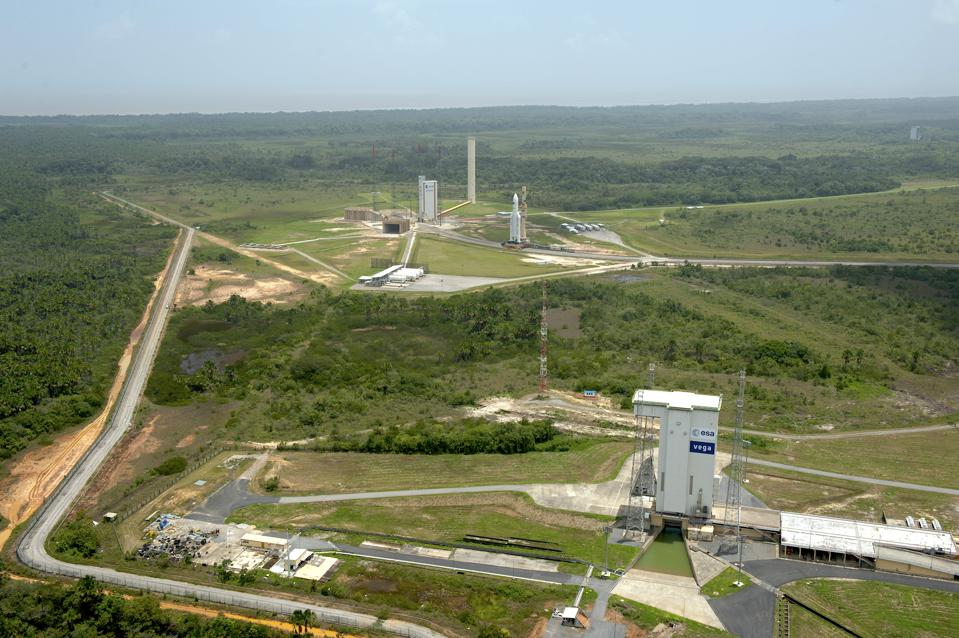 Aerial view of Vega and Ariane 5 launch pads at Europe's Spaceport in Kourou, French Guiana. An Ariane 5 is shown in the background, during its transfer from the BAF (Final Assembly Building) to the Spaceport's ELA-3 launch zone, in March 2012.