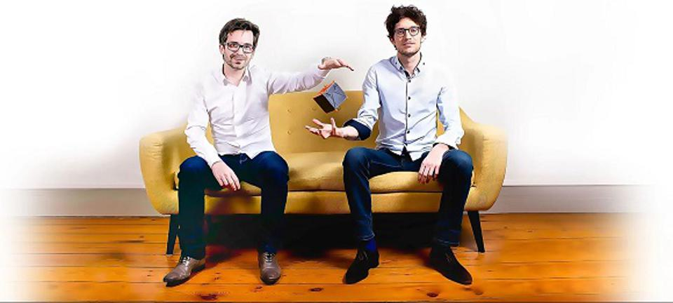 Two businessmen sat on a sofa, one dropping a cube into the other one's hand.