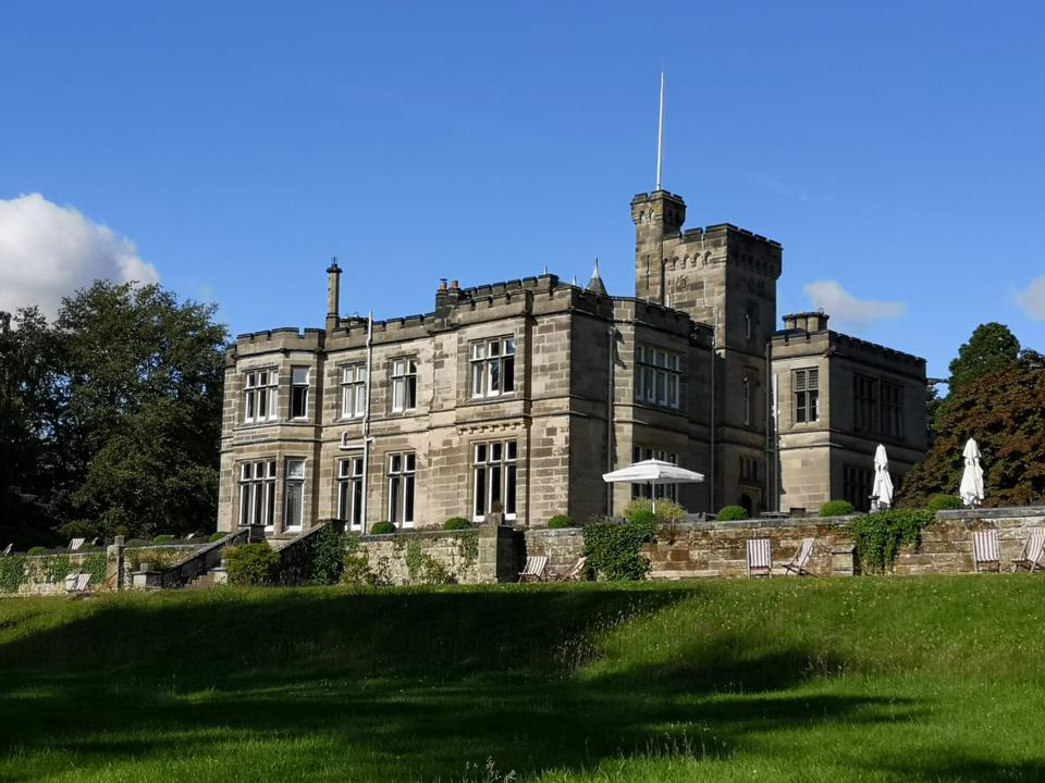 stone manor house with green lawn and blue sky