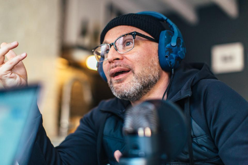Derek Drescher with headphones at podcast