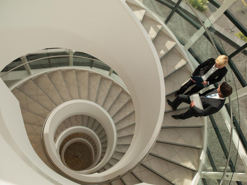 Two business types confer on a spiral staircase which may lead to evil underground lair.