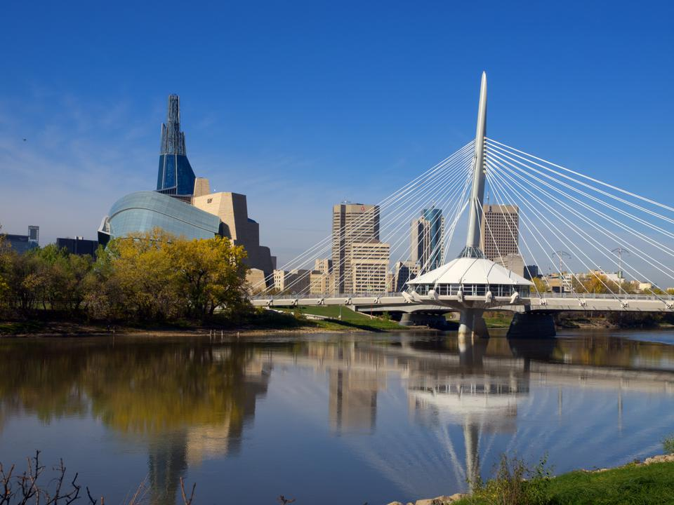The exterior of the Canadian Museum for Human Rights and a suspension bridge over the river in downtown Winnipeg, Manitoba