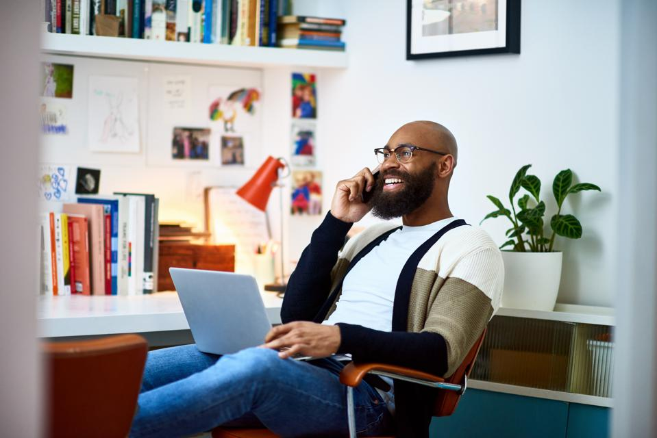 Man working from home talking on phone.