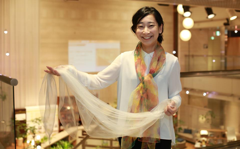 Smiling japanese woman holding a scarf