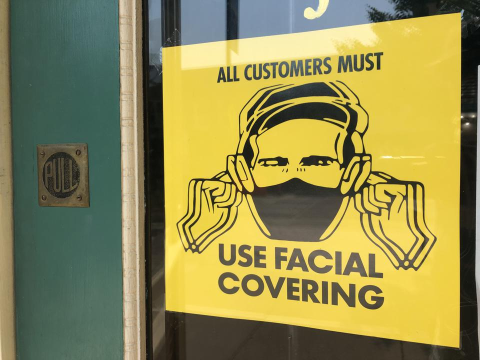Yellow sign mandating face coverings in Lawrence, Kansas.
