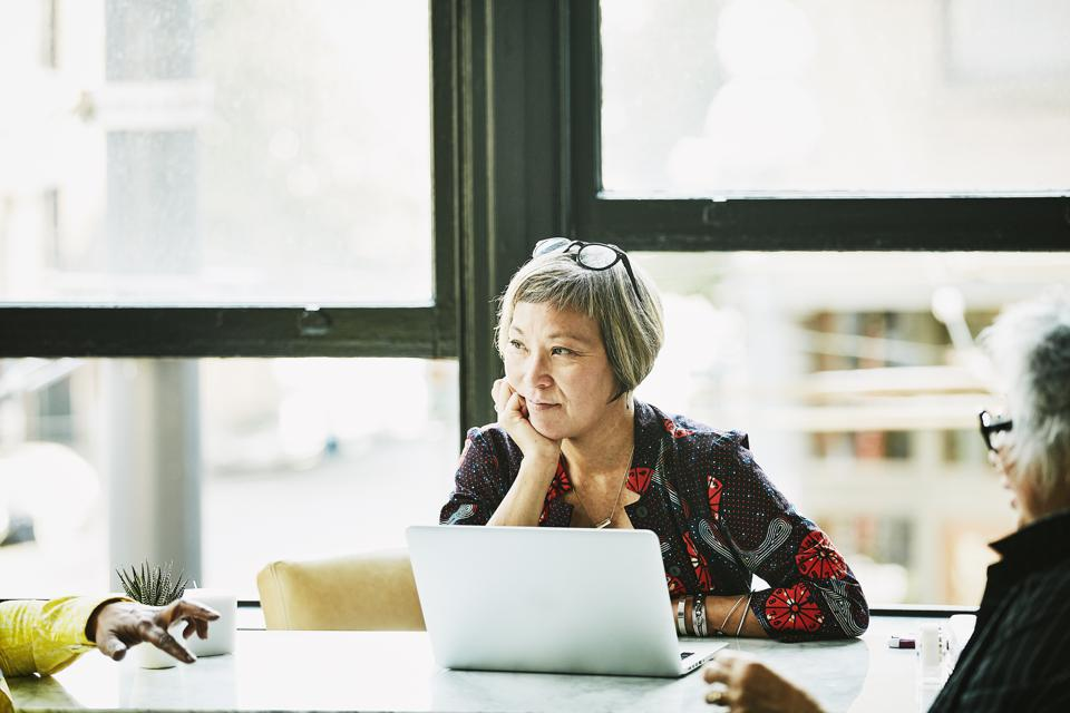 Mature businesswoman listening during meeting with clients in office
