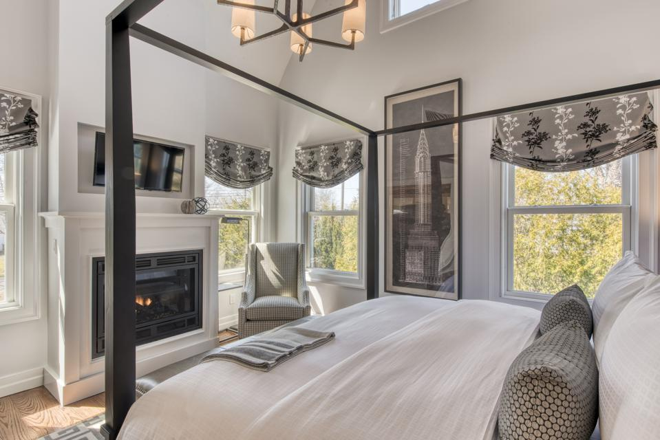 An elegant grey and white bedroom with fourposter bed at the South Harbor Inn